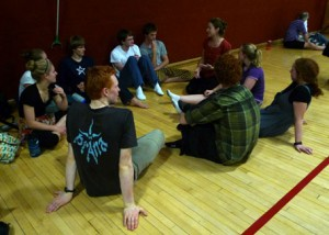 Mary talking with a bunch of young folks at a contra dance (photo by Sarah Babbitt Spaeth)